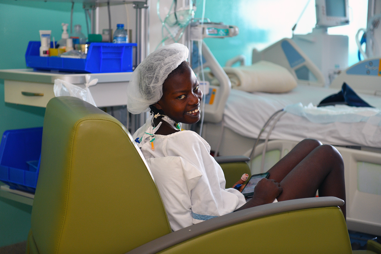 Wideline sits up smiling days after her mitral valve repair surgery.